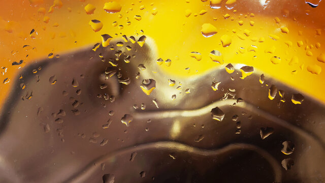 Abstract scenic background with raindrops on glass, city illuminated neon lights. Bright colors of yellow brown colors.