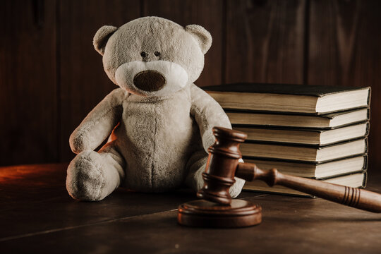 Divorce and alimony concept. Wooden gavel and teddy bear as symbol of child on a desk.