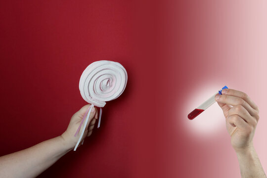closeup female hand holding marshmallow candy on a stick, red background, medical concept of blood sugar control, sweets, healthy lifestyle