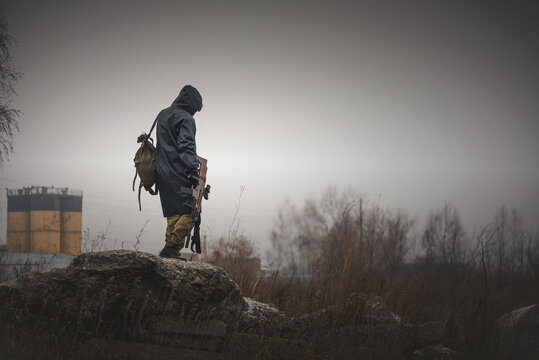 A post apocalypse soldier is walking on a abandoned area with a rifle and backpack.