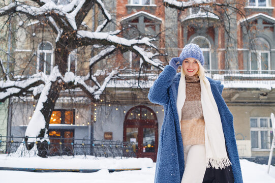 Happy smiling woman posing in street of European city. Model wearing blue faux fur coat, hat, white scarf. Winter, Christmas, New Year holidays, travel conception. Copy, empty space for text