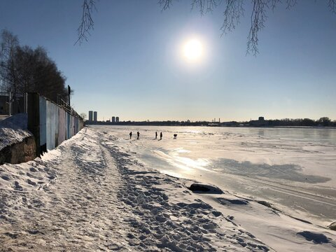 Suny day in winter and people on the river ice