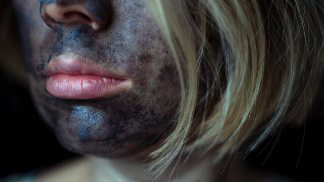 women's lips and a cleansing charcoal mask on her face