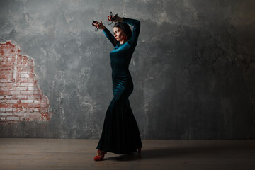 Young adult spanish woman dancing flamenco on gray vintage background