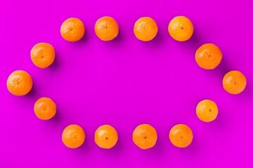 Fruit pattern of fresh orange tangerine or mandarin on lilac background. Flat lay, top view. Pop...