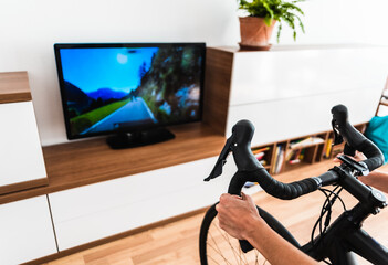 Cycling Indoor with exercise bike trainer motivating himself with the gamification of sport.
