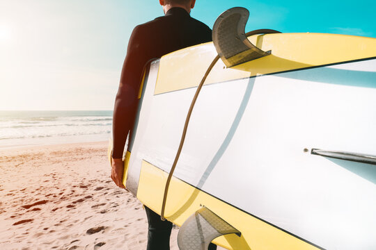 Surfer in wetsuit holding yellow surfboard on the beach near the ocean