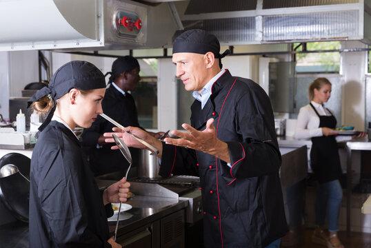 Exasperated head chef scolding upset female employee in kitchen of restaurant..