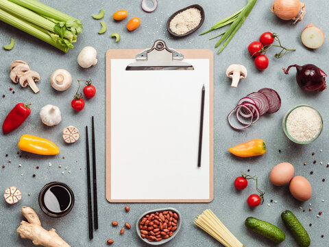 Asian ingredients and clipboard with white paper sheet. Various of Chinese cooking ingredients and chopsticks on gray stone background. Asian food concept. Copy space for text. Top view or flat lay.