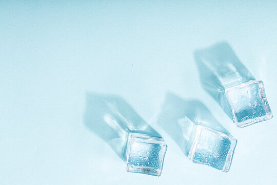 Ice cubes on vibrant light blue colors. Concept art. Minimal surrealism. Flat lay with copy space. Soft focus.