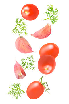 Isolated vegetables and herbs. Seven pieces of tomato, dill, and garlic falling down isolate on white with clipping path as package design element. Full depth of field. Food levitation concept.