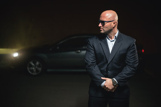 A serious driver in a suit is standing at night on a parking area.