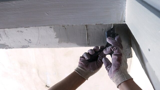 leveling the upper corner of the doorway with the hand of a professional in a glove holding a trowel, part of the process of interior decoration of the house during a major renovation