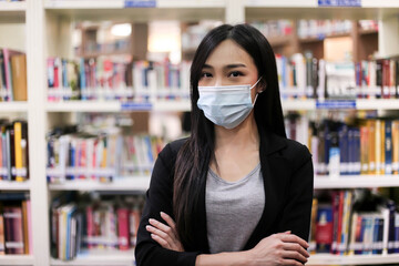 Beautiful Asian librarian woman  wear face masks  to prevent coronavirus, or COVID-19 new normal...