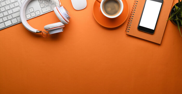 Top view of stylish workspace with smart phone, head phone, coffee cup, notebook and copy space on orange background.