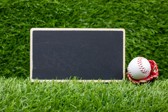 Baseball with chalkboard are on green grass