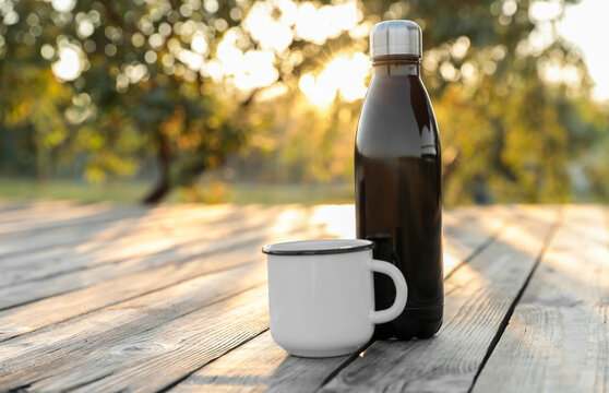 Modern black thermos bottle and cup on wooden surface outdoors. Space for text