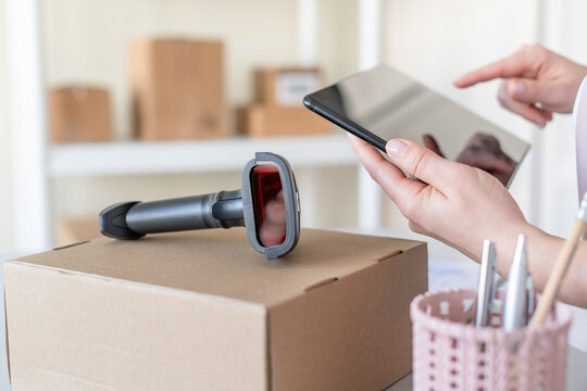 Female owner of start up small business using tablet, barcode scanner scanning retail drop shipping package postal parcel bar code. Warehouse worker.