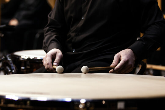 Hands of a musician playing the timpani in the orchestra close up