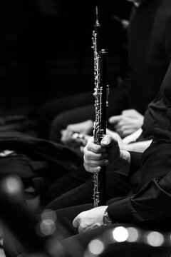 Oboe in the hands of a musician in an orchestra in black and white