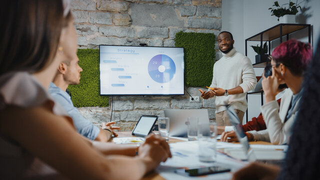 Office Conference Room Meeting: Black Chief Company Strategist Doing TV Presentation to a Diverse Team of Multi-Ethnic Professional Businesspeople, Explaining Marketing Strategy, Data Analysis