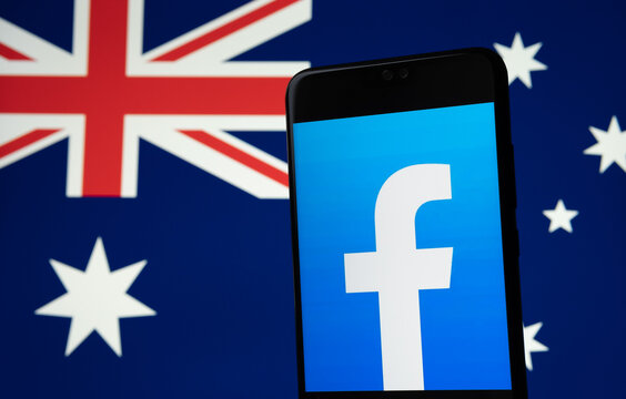 Facebook logo seen on the smartphone and blurred Australian flag on the background screen. Concept. Stafford, United Kingdom, February 18, 2021.