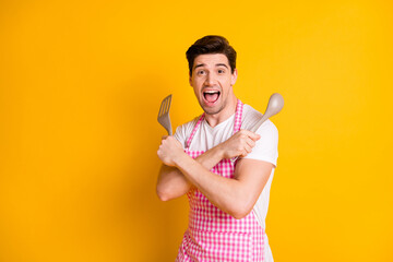 Obraz Photo of positive young man crossed hands hold spatula spoon open mouth shout loud isolated on yellow color background - fototapety do salonu