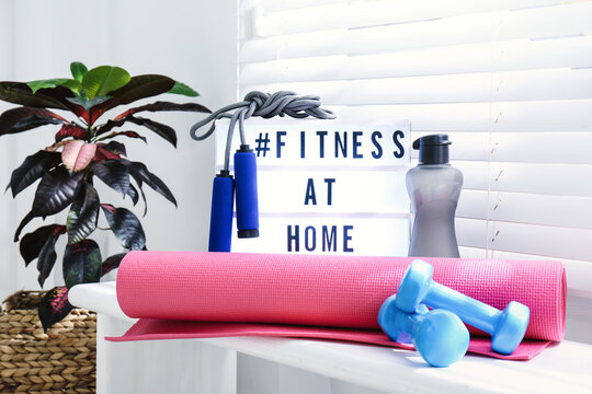 Sport equipment and lightbox with hashtag FITNESS AT HOME on window sill indoors. Message to promote self-isolation during COVID‑19 pandemic