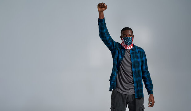 Proud young african american male protester, activist wearing bandana mask with american flag print looking at camera, posing with arm raised isolated over gray background