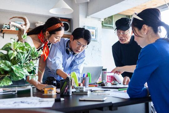 図面を広げて会議をする建築事務所のチーム