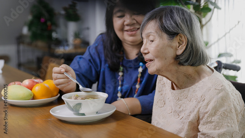 Mother's day ,Daughter feeding elderly mother with soup.