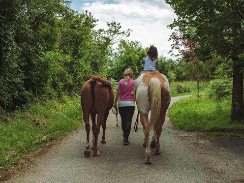 mujer con dos caballos y preciosa niña montando en uno de ellos