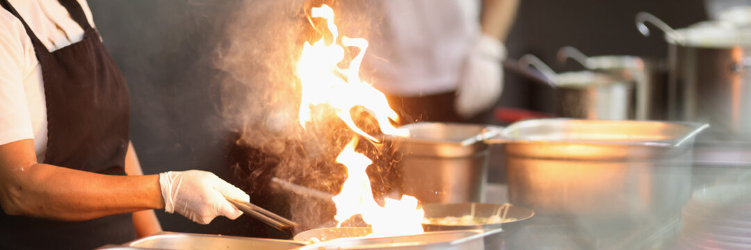 Cook prepare food on fire. Hot flame in pan. Kitchen has lot of kitchen utensil. Self-service restaurant.
