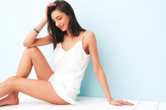 Portrait of beautiful smiling woman dressed in white pajamas. Sexy carefree cheerful model enjoying her morning. Adorable and positive female sitting near light blue wall in studio. Tanned and skinny