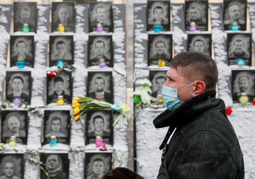 A man visits a monument to the people killed during the Ukrainian pro-European Union protests in Kyiv