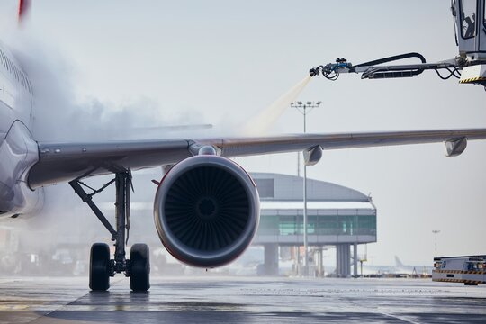 Deicing of aircraft wing before flight. Winter frosty day at airport.