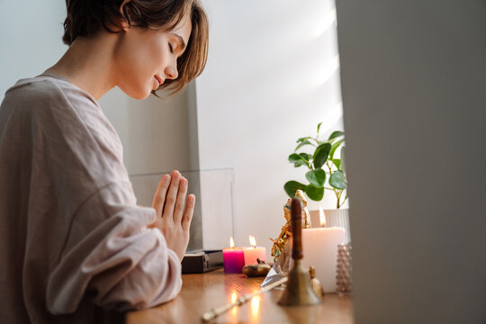 Peaceful beautiful girl praying at home shrine indoors