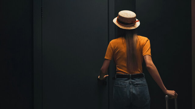 back view of tourist in straw hat standing with luggage near door in hotel room