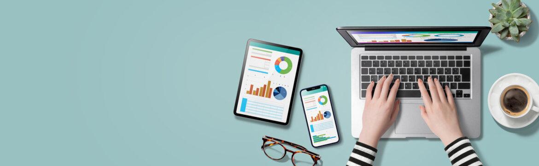 ノートパソコン、スマートフォン、タブレット端末のツールを使って仕事をしている人物のイメージビジュアル。真上から見たアングル。