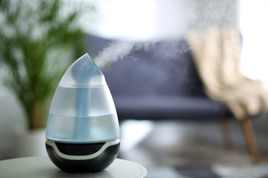 Modern air humidifier on table indoors. Space for text