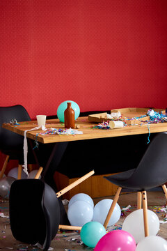After party chaos, messy in livving room at home, table with pizza and champagne glasses covered with confetti and ballons, chair on the floor at morning after party celebration.