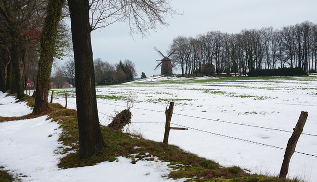 The old windmill on the hill is seen in the background. A snow covered meadow, barbwire fence and some trees in front.  A scenic winter landscape in Germany near the Dutch border.
