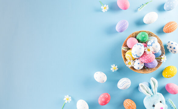 Happy easter! Colourful of Easter eggs in the nest with rabbit on pastel blue background. Greetings and presents for Easter Day celebrate time. Flat lay ,top view.