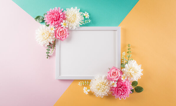 Happy women's day concept, beautiful flower with picture frame on pastel background. Flat lay ,top view with space.