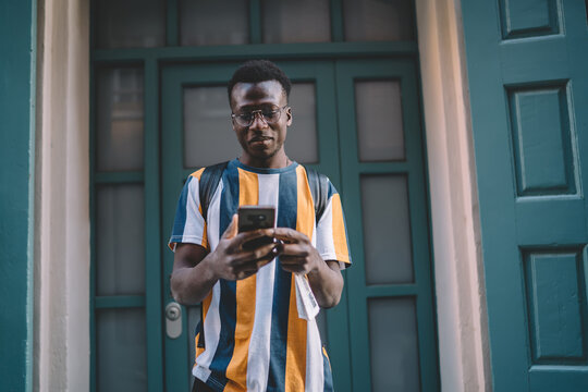 African American male blogger making online booking and banking via modern cellphone gadget, millennial generation Z in trendy spectacles searching application for installing on smartphone device