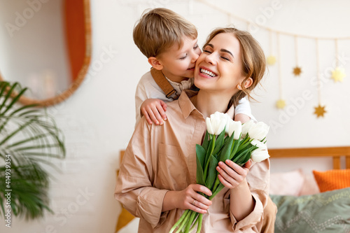 tender son kisses the happy mother and gives her a bouquet of tulips, congratulating her on mother's day