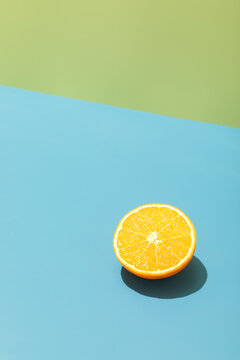 Slice of ripe yellow lemon on a bright blue and green background, hard light