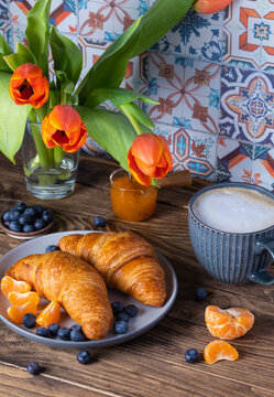 Breakfast with croissants, fresh blueberries, tangerines and coffee on the wooden background