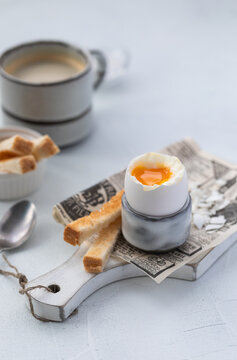 Soft-boiled egg in an eggcup with toasts and coffee on the wooden background