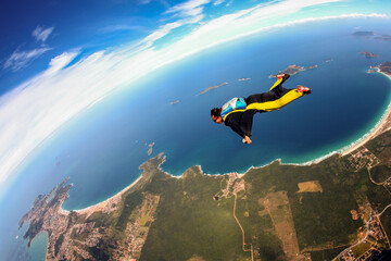 Fototapeta Skydiving wing suit flying over Brazilian beach